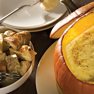 Artichoke and fall fruit fondue in a pumpkin